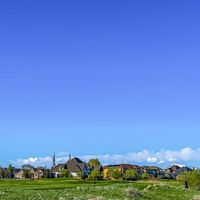 Square frame Vast grassy terrain with houses under blue sky and puffy clouds on a sunny day