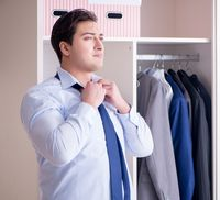 Young man businessman getting dressed for work