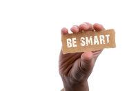 Be smart wording in hand on torn notepaper in hand