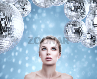 Young beautiful woman portrait with abstract mirror disco balls design background
