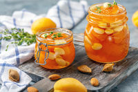 Apricot homemade jam with almonds in glass jars.