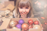 Cute girl and a box of Christmas decorations