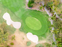 Birds eye view of golf course hole green and sand traps.