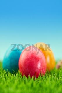 Drei Ostereier auf Wiese zu Ostern im Garten