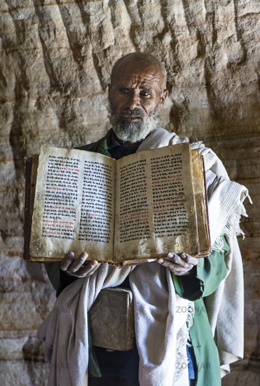 Orthodox priest of the rock-hewn church Mikael Mellehayzengi showing the book Miracles of Maria