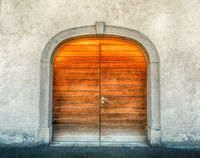 massive winged wooden door in a stone wall with a granite door arch