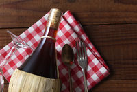 A basket bottle of Chianti wine on a red and white checked napkin with fork and spoon