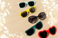 different sunglasses on beach sand