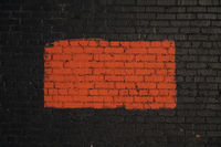 Red rectangle painted on black brick wall