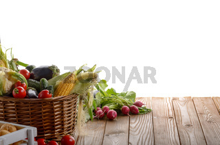 Basket of Organic vegetable food ingredients and crate of potatoes on white background