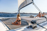 People relaxing on a summer sailing cruise, sitting on a luxury catamaran near picture perfect Palau town, Sardinia, Italy.