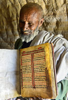 Orthodox priest of the rock-hewn church Mikael Mellehayzengi showing a hand-written book,Ethiopia