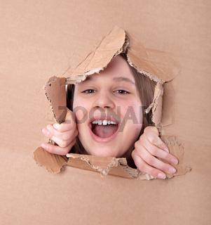 kid portrait in torn paper hole