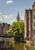 Ghent, Belgium - June 13, 2017: The clock tower of the old postal building with of the canals in the foreground