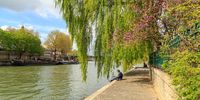 Paris, France, April 1 2017: People enjoy sun light by River Seine. With the population of 2M, Paris is the capital and most-populous city of France