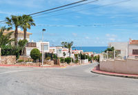 Roadside view to the empty road leading to Mediterranean Sea, coastal summer villas residential houses, blue cloudy sky, picturesque landscape. La Mata, Province of Alicante, Costa Blanca, Spain