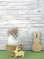 Easter background with Easter egg and Easter bunnies  isolated on green in front of wood