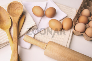 Overhead view of eggs and kitchen tools on table