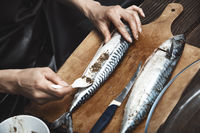 Woman preparing mackerel fish