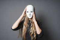 mysterious young woman adjusting her mask