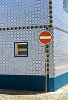 Traffic sign No entry for vehicular traffic in front of a residential building with a tiles fassade