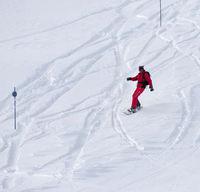 Snowboarder descends on snowy ski slope