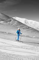 Skier on snowy ski slope at nice sun day