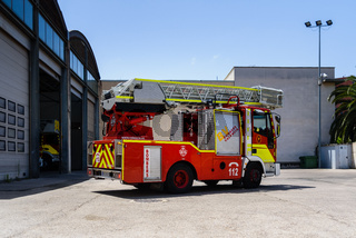Valencia, Spain - June 8, 2019: Fire truck with ladder leaving the fire station to help in an emergency.