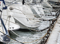 White Yachts Tied Up With Ropes To A Pier