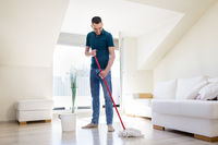 man with mop and bucket cleaning floor at home