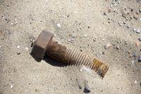 rusty screw on the sandy beach