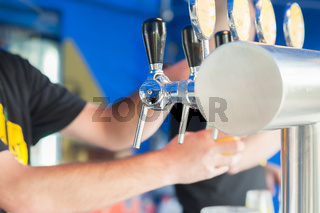Draught draft beer taps in a bar .