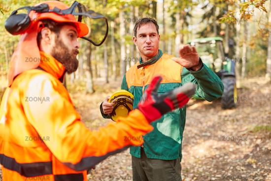 Zwei Waldarbeiter besprechen die Holzernte