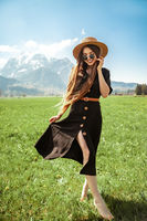 Beautiful girl in dress and hat on meadow in mountains.