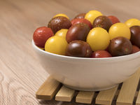 Cherry tomatoes in a variety of colors in ceramic bowl on wooden background.