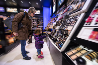 young mother and her little daughter buying makeup