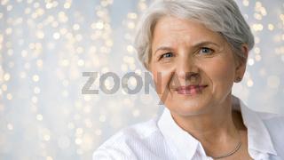 portrait of senior woman over festive lights