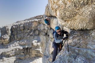 two mountain climbers on an exposed Via Ferrata in the Dolomites of Italy