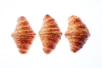 Set of three homemade french croissants on a white background.
