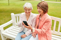 happy senior women with smartphone at summer park