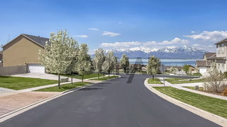 Panorama Neighborhood street with view of lake snow capped mountain and cloudy blue sky