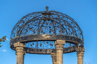 Cast iron gazebo with dome roof supported by five white stone pillars