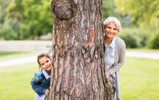 grandmother and granddaughter behind tree at park