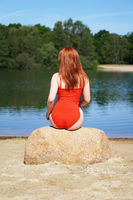 rear view of young woman wearing red swimsuit or bathing suit sitting on rock on beach at idyllic lake