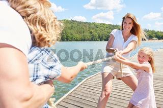 Familie mit Kindern hat Spaß beim Tauziehen