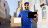 delivery man with tablet pc and parcel in city