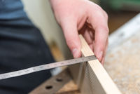 Carpenter misses with tape measure wooden board - closeup workplace