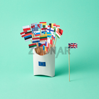 Paper flag of Britain and a cardboard box with a sign of the EU and different flags on a green background with copy space. The exit of Britain from EU