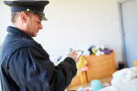 Polizist der Kriminalpolizei am Tatort nach Einbruch