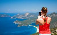 young woman taking a photo of beautiful sea on smartphone, in Oludeniz, Turkey